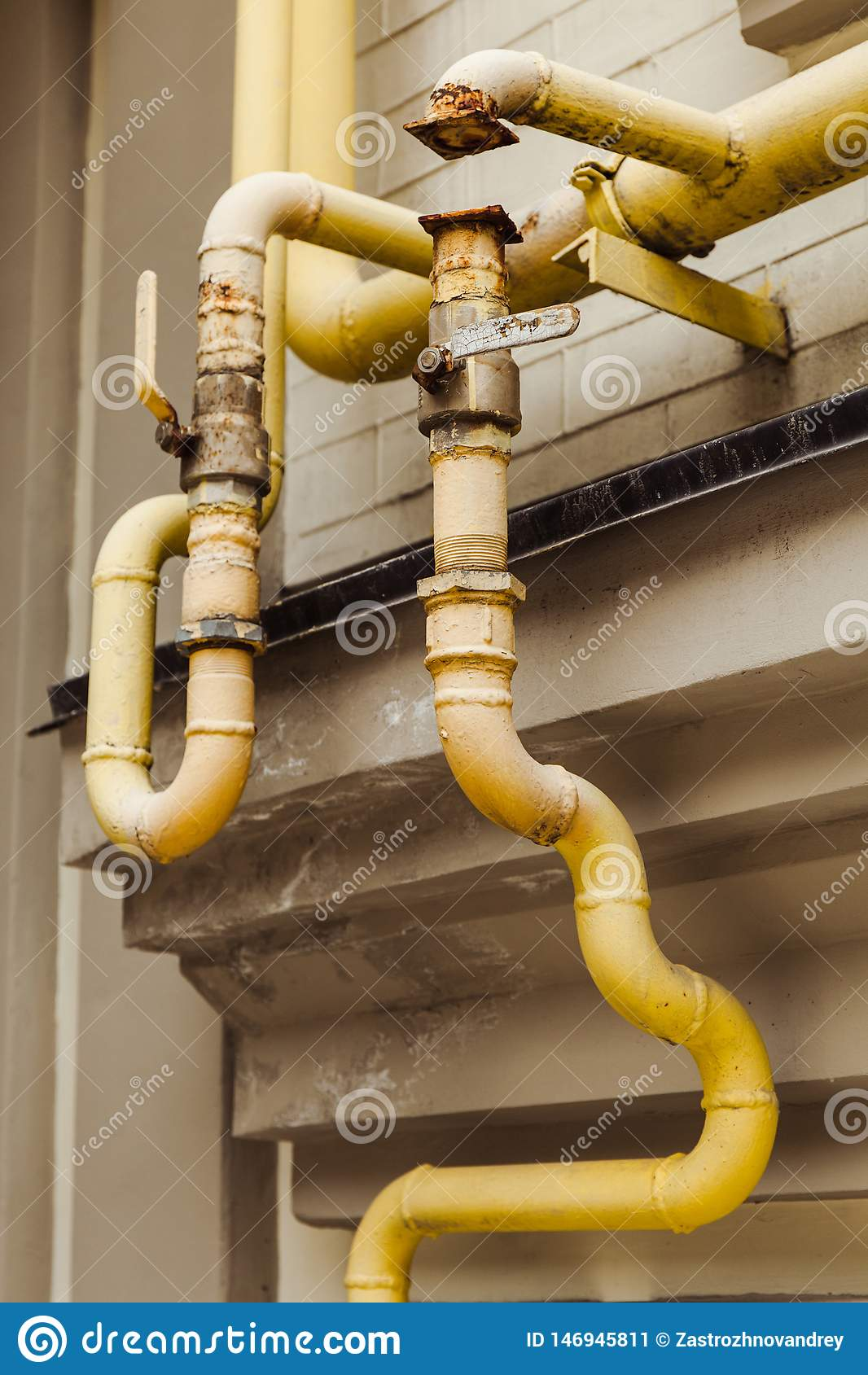 Старые изогнутые желтые трубы на старом доме