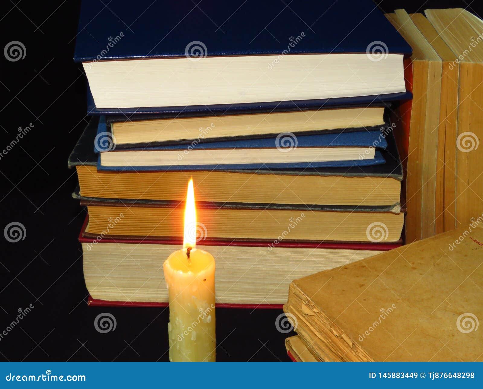 Старые книги штабелированные в куче и горящей свече Образование, знание, привычки чтения, бумага, библиотека, свет, пламя, тайна