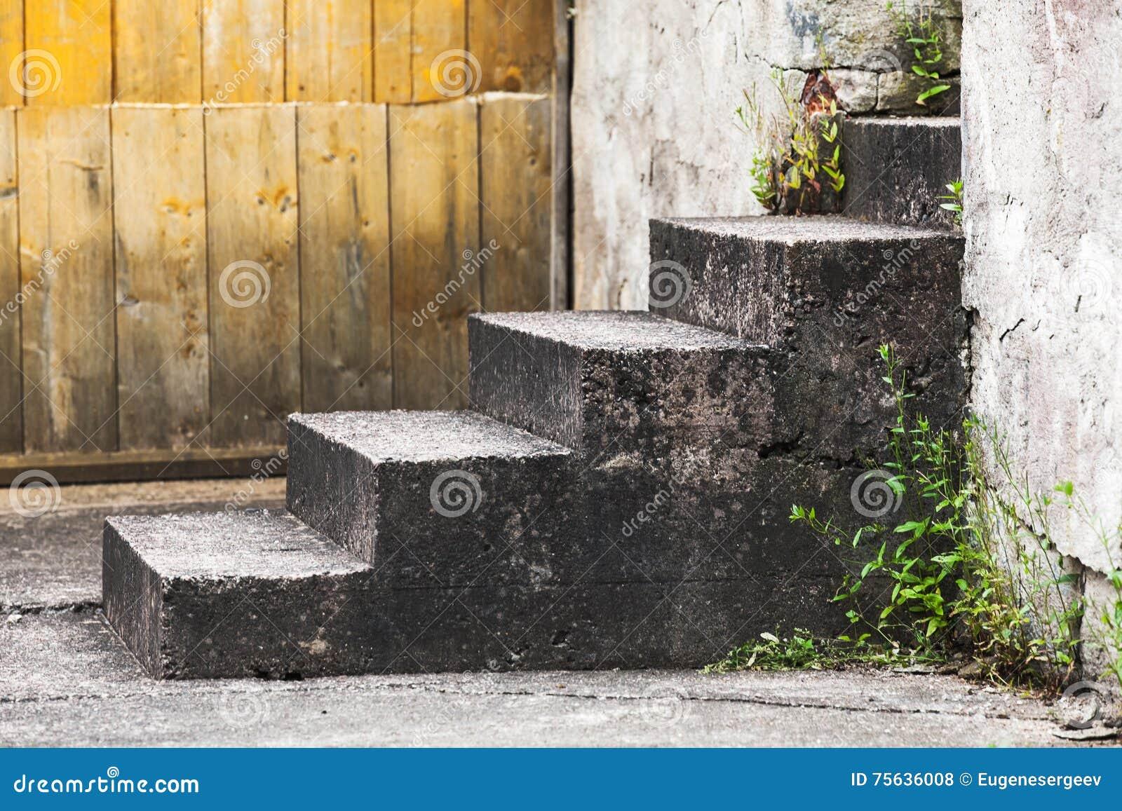 Старые конкретные лестницы около деревянной стены