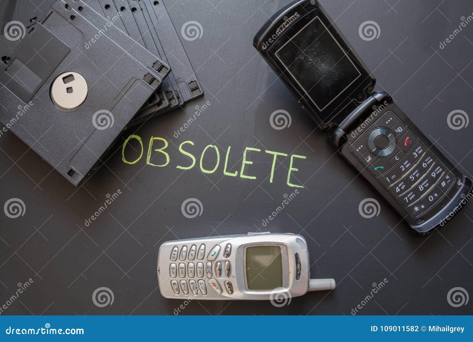 Старые мобильные телефоны и гибкие магнитные диски на темной предпосылке