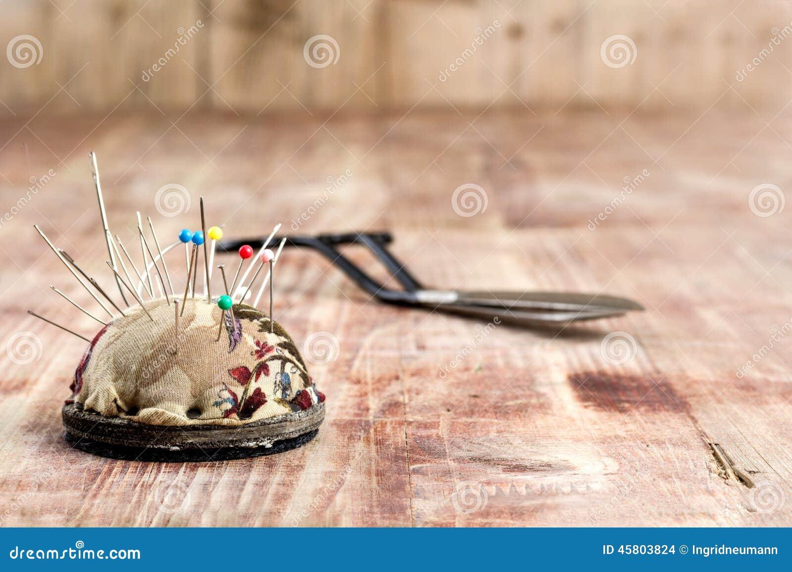 Старые ножницы и pincushion на деревянной предпосылке