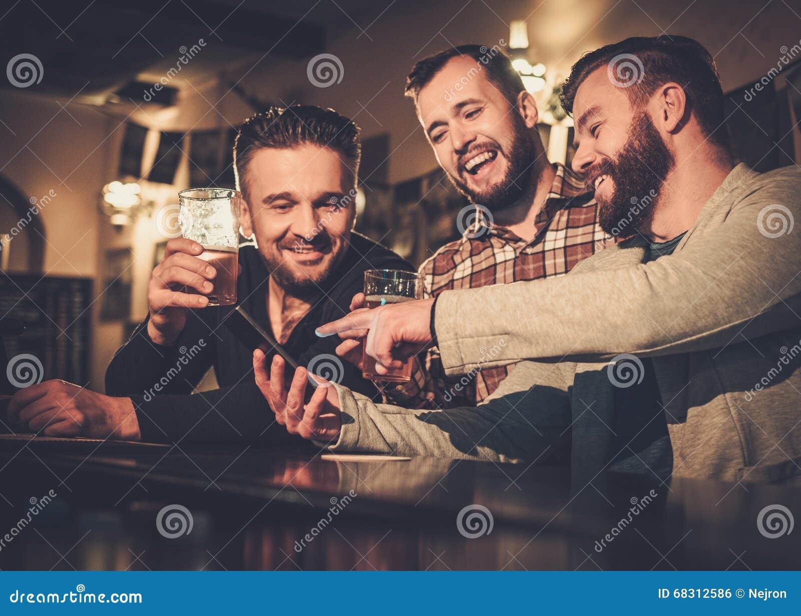 Старые други имея потеху с smartphone и выпивая пиво проекта на счетчике бара в пабе