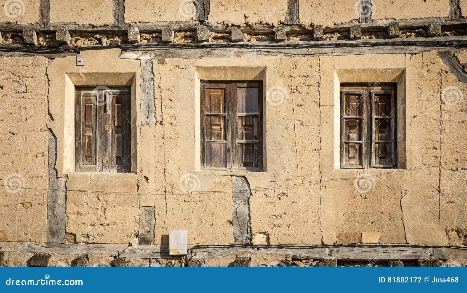 Старые сломанные деревянные окна на покинутом деревенском доме сделанном из древесины и глины