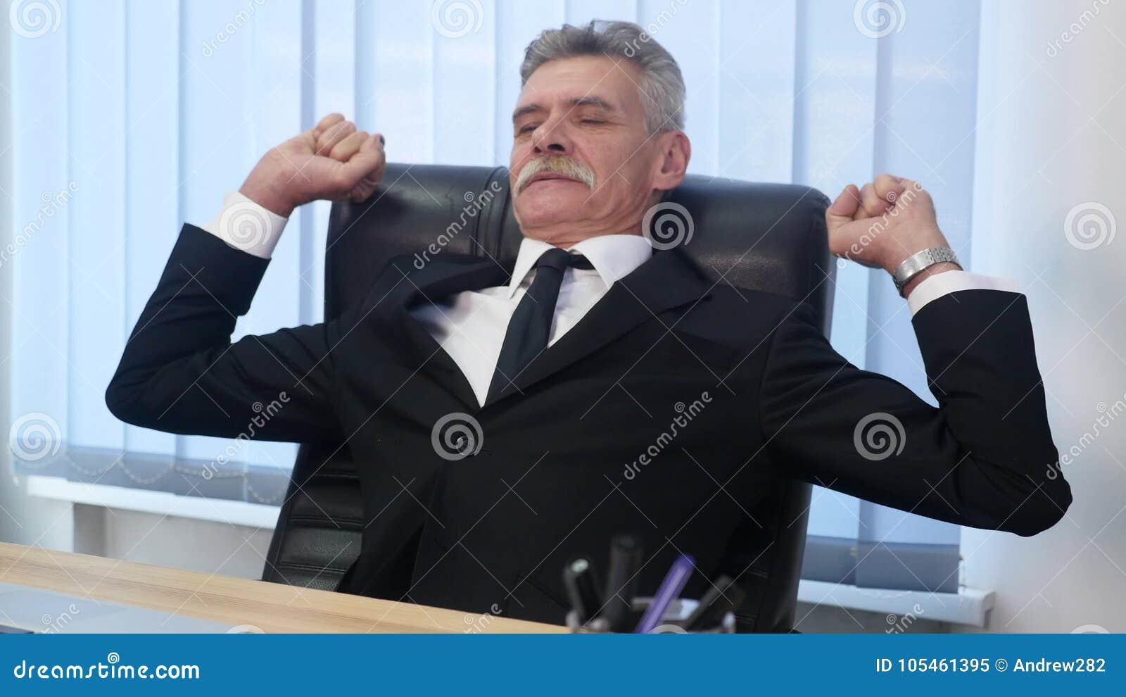 Старый бизнесмен положился назад в его стуле офиса, он усмехается и daydreaming