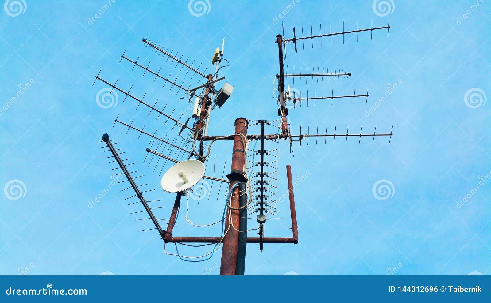 Старый винтажный ржавый рангоут телевидения с много антенн указывая н