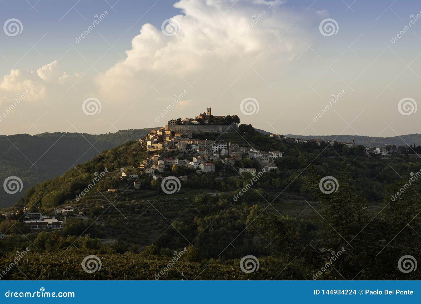 Старый городок Motovun в Istria поднимает вверх на холм в заходе солнца поздн