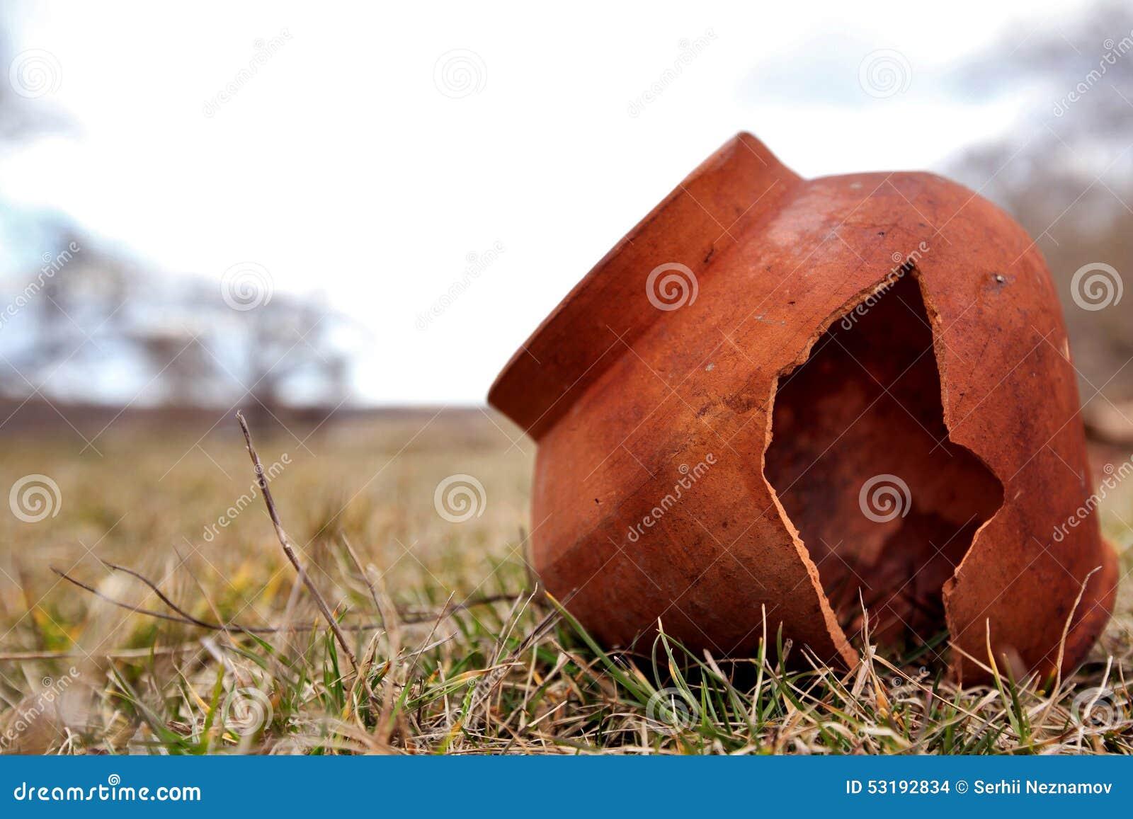 Старый глиняный горшок разделен в поле Покинутое исконное плитки Глиняный горшок сломленн