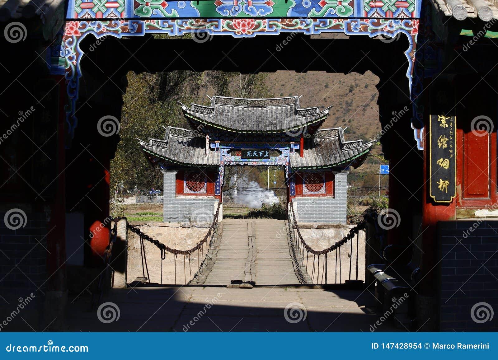 Старый деревянный висячий мост вдоль старого южного шелкового пути в деревне Shigu в провинции Юньнань, Китая