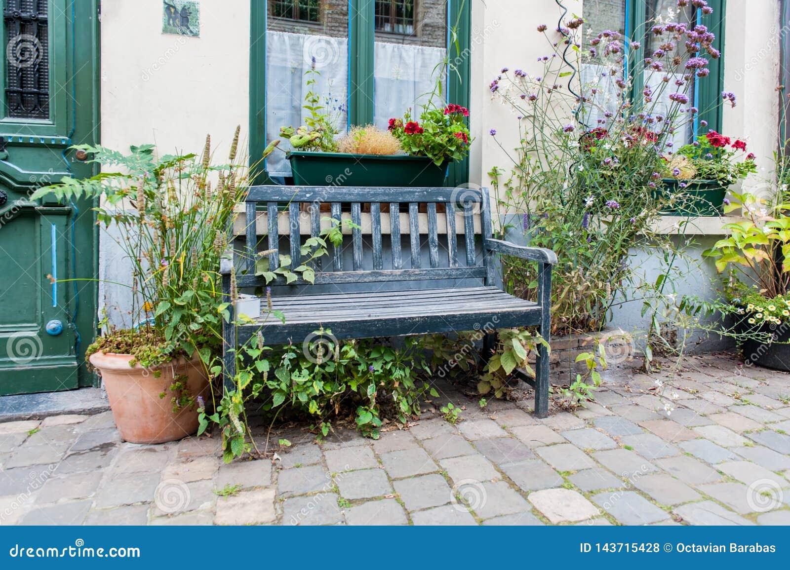 Старый и выдержанный деревянный стенд перед домом с цветочным горшком
