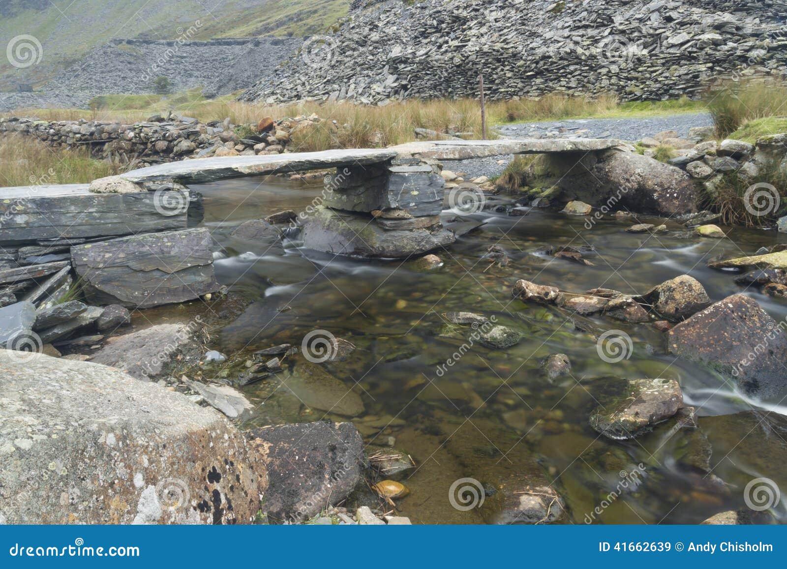 Старый каменный мост колотушки над потоком горы
