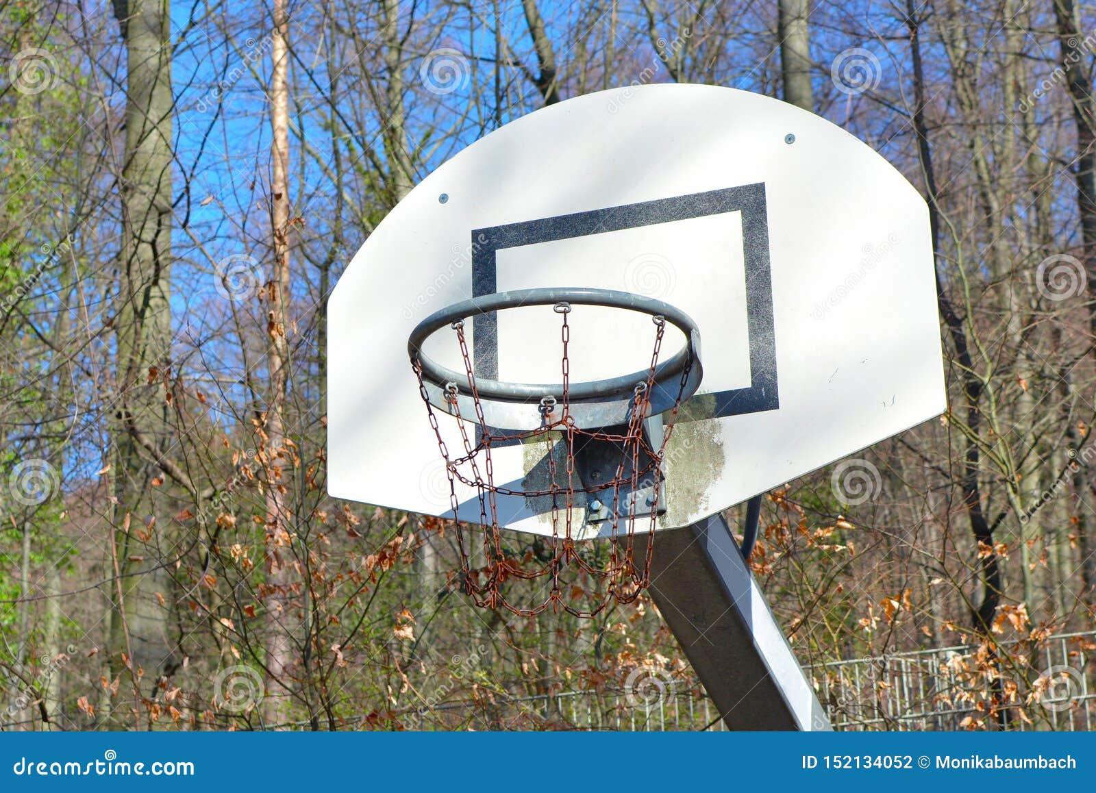 Старый, который побежали спуск и ржавая корзина баскетбола на земле игры окруженной лесом