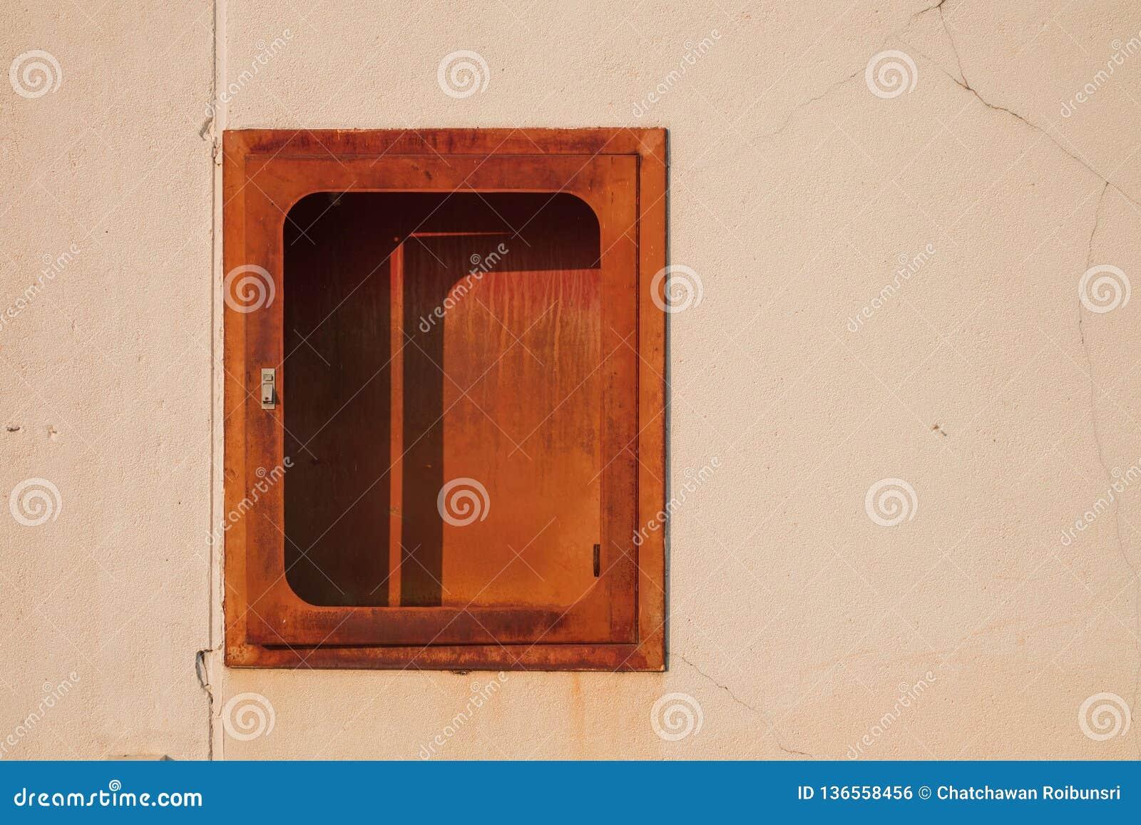 Старый красный огнетушитель на белой стене