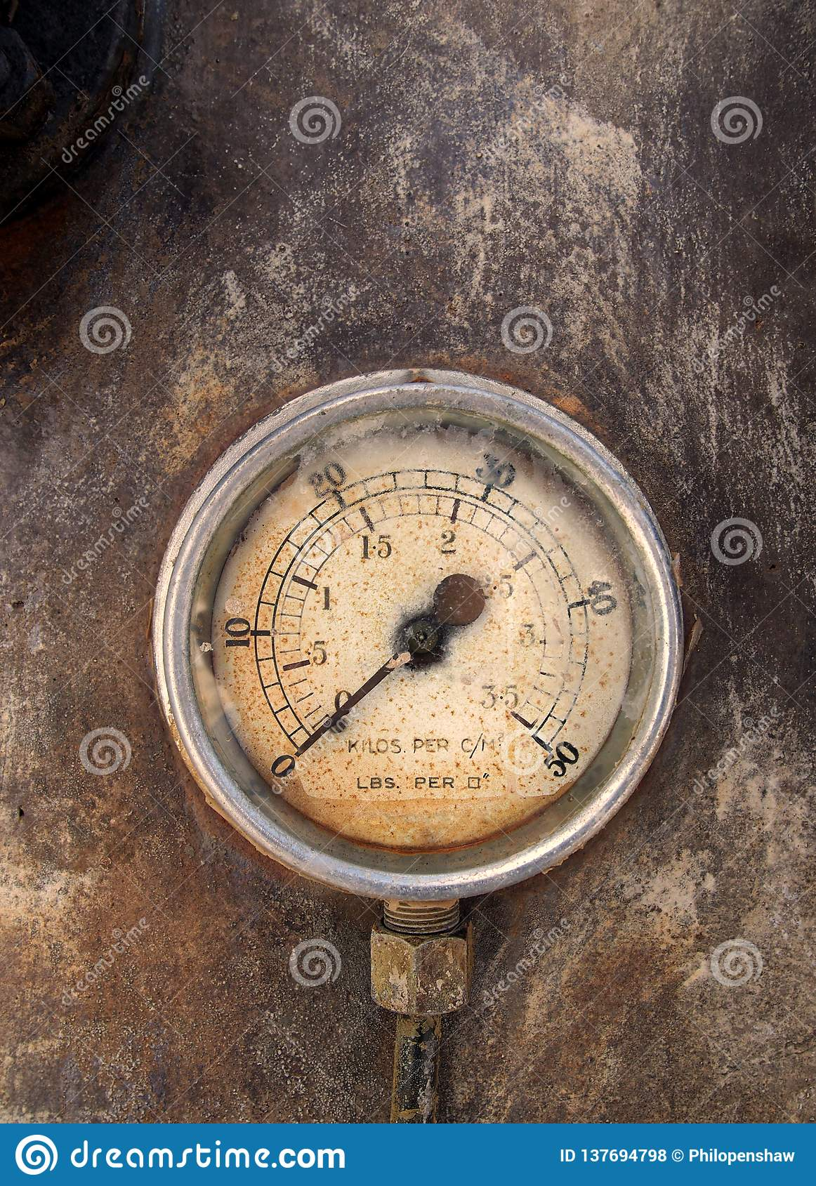 Старый круглый метр давления с номерами на датчике на ржавой предпосылке металла