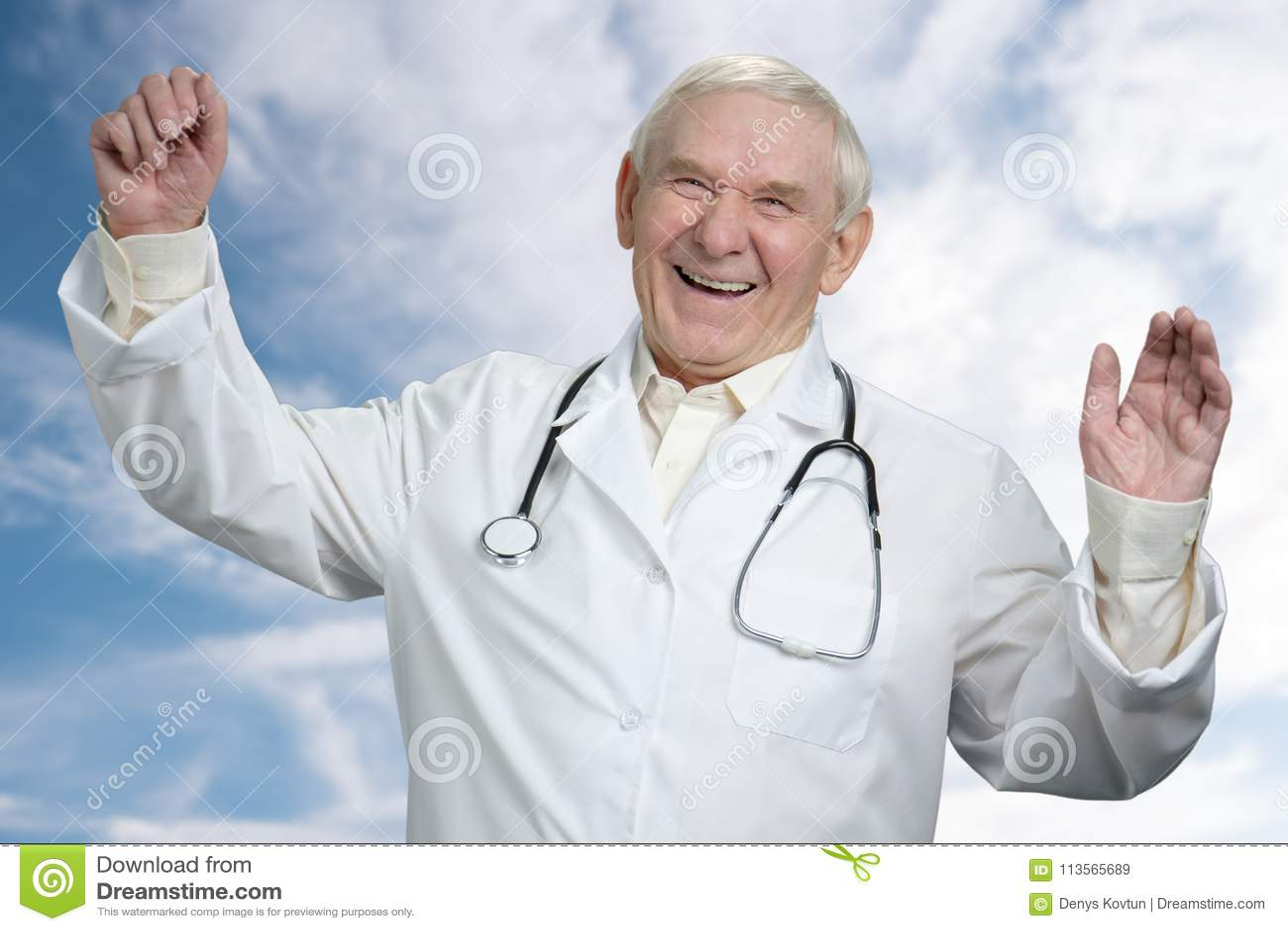 Старый мужской доктор смеясь над вне громко с руками вверх