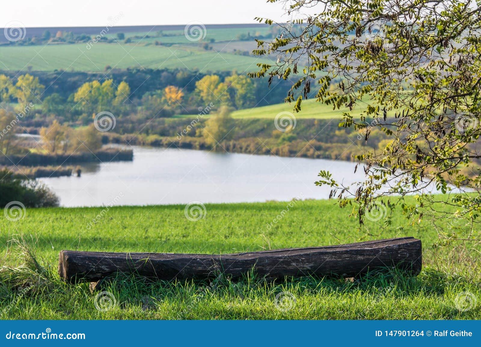 Старый стенд перед красивым холмистым ландшафтом с озером
