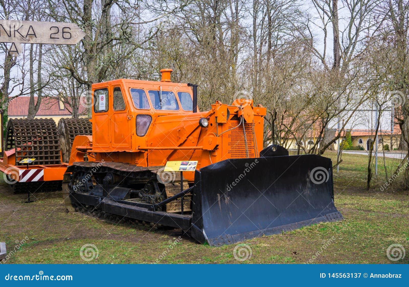 Старый трактор для уносить сельскохозяйственные работы в поле на ферме r latvia