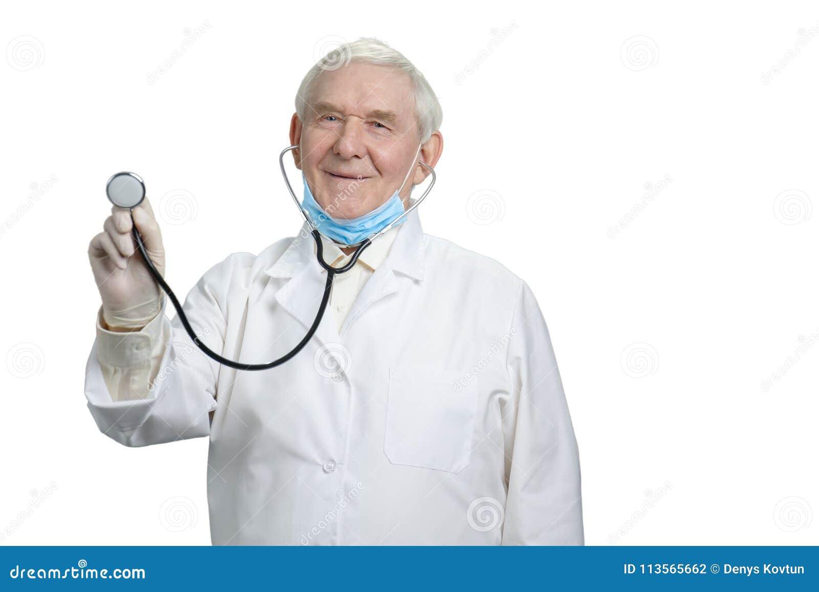 Старый усмехаясь доктор с слушает ваше биение сердца используя стетоскоп