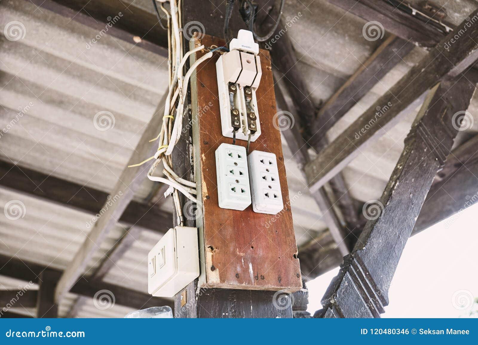 Старый электрический выключатель силы переключения и выход AC штепсельные вилки на деревянной доске