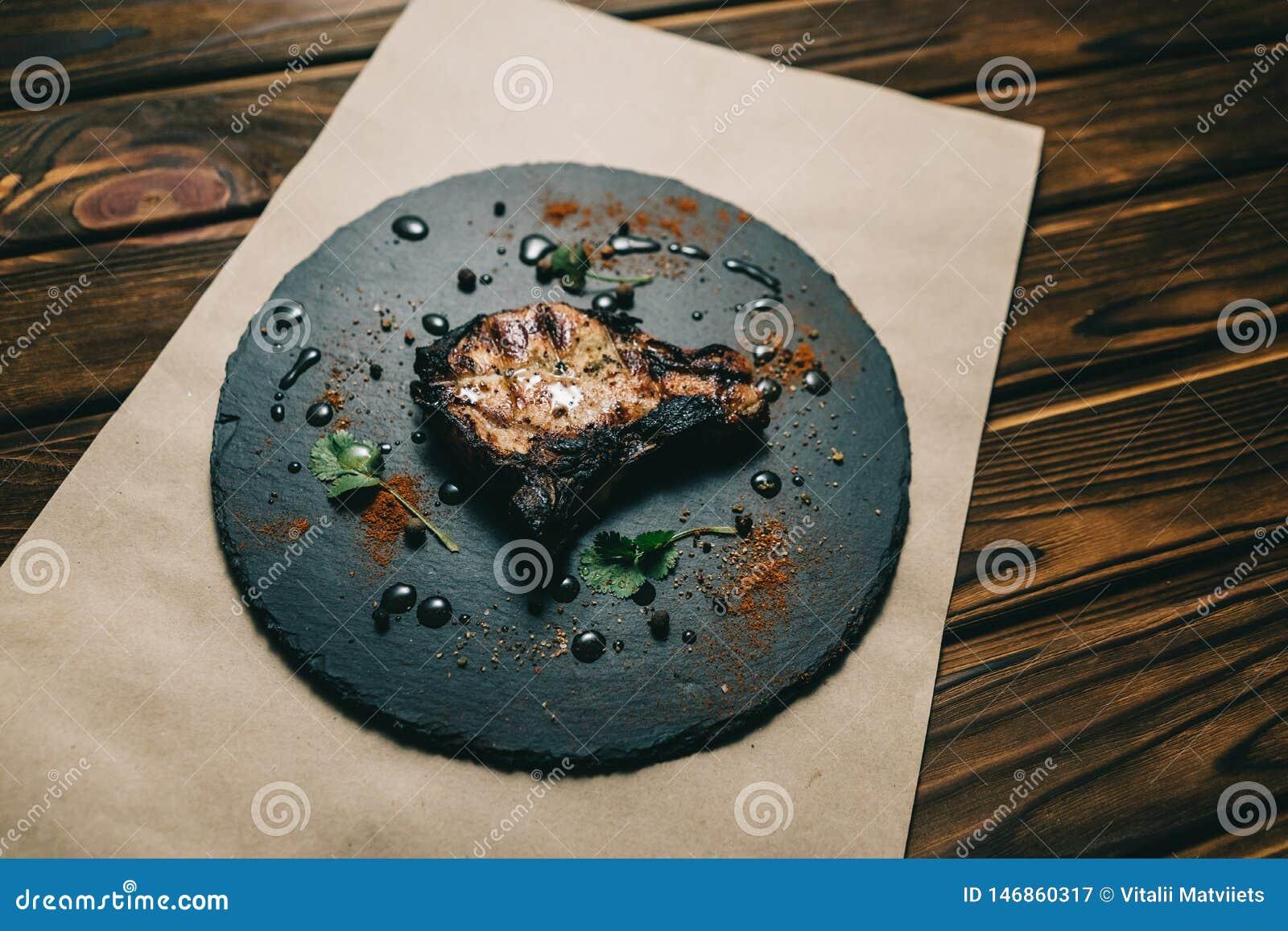 Стейк косточки свинины на деревянной предпосылке с медом Шифер доски kenza, перец
