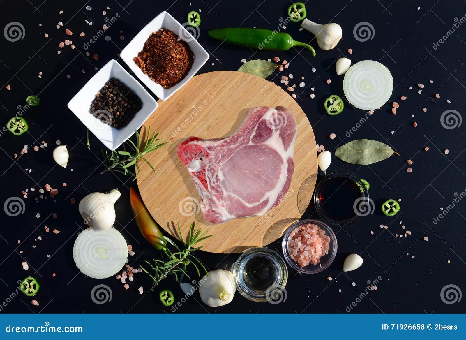 Стейк мяса на разделочной доске и перце, лист залива, розмариновом масле, луках, соли, оливковом масле, соевом соусе