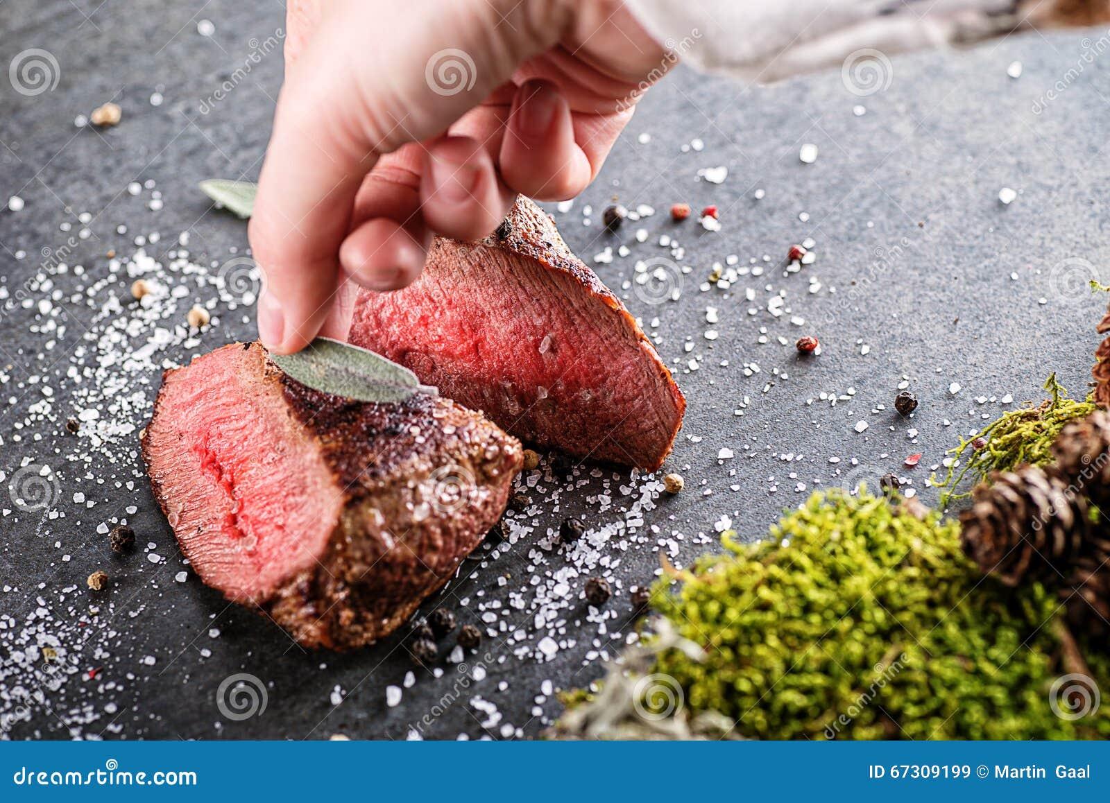 Стейк оленей или оленины с ингридиентами любит соль моря, травы и шеф-повар перца и руки, предпосылка еды для ресторана или lo зв