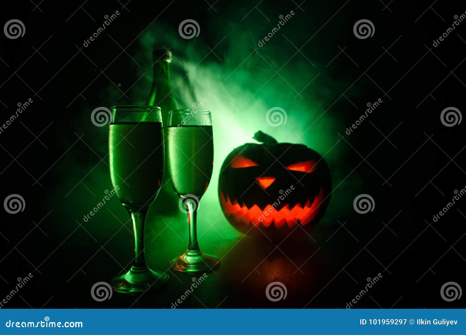 2 стекла вина и бутылки с хеллоуином - старого Джек-o-фонарика на темной тонизированной туманной предпосылке тыква halloween стра