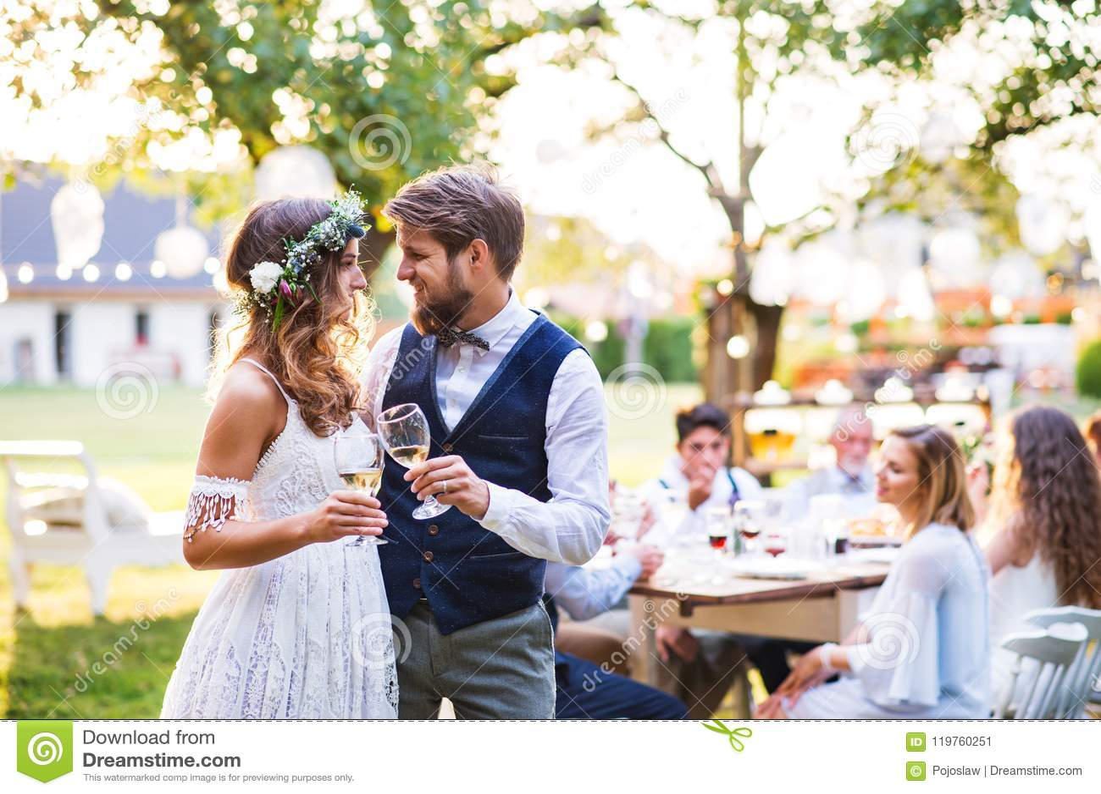Стекла жениха и невеста clinking на приеме по случаю бракосочетания снаружи в задворк