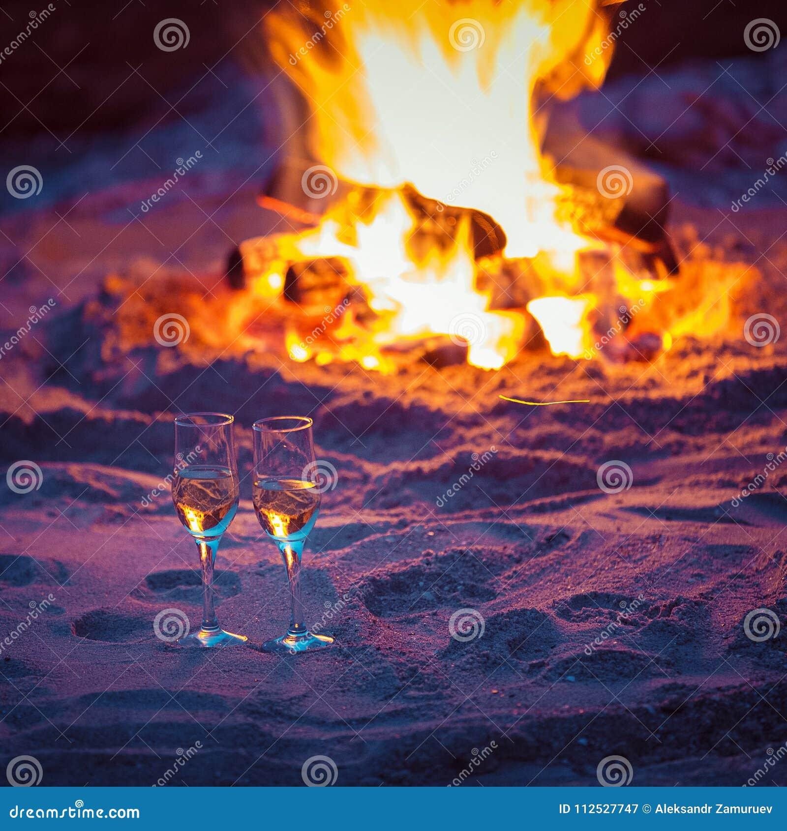 2 стекла игристого вина перед теплым камином на песке моря