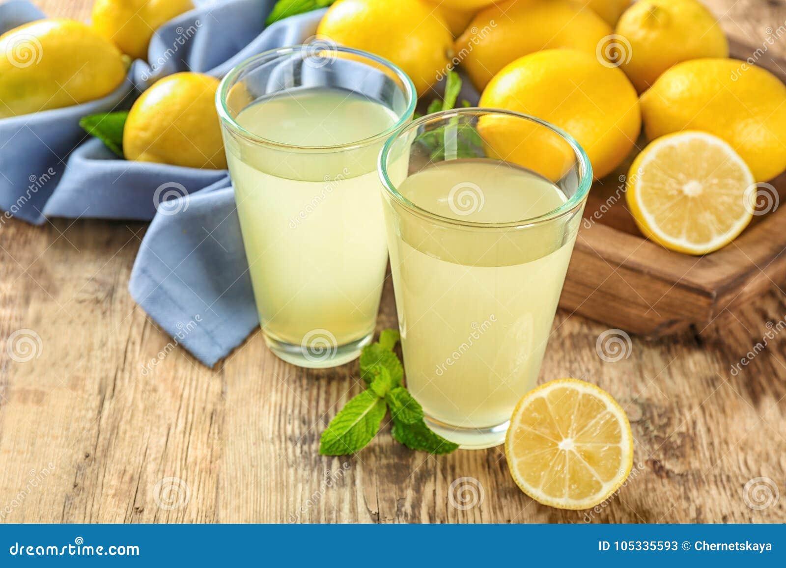 Стекла лимонного сока и свежих лимонов