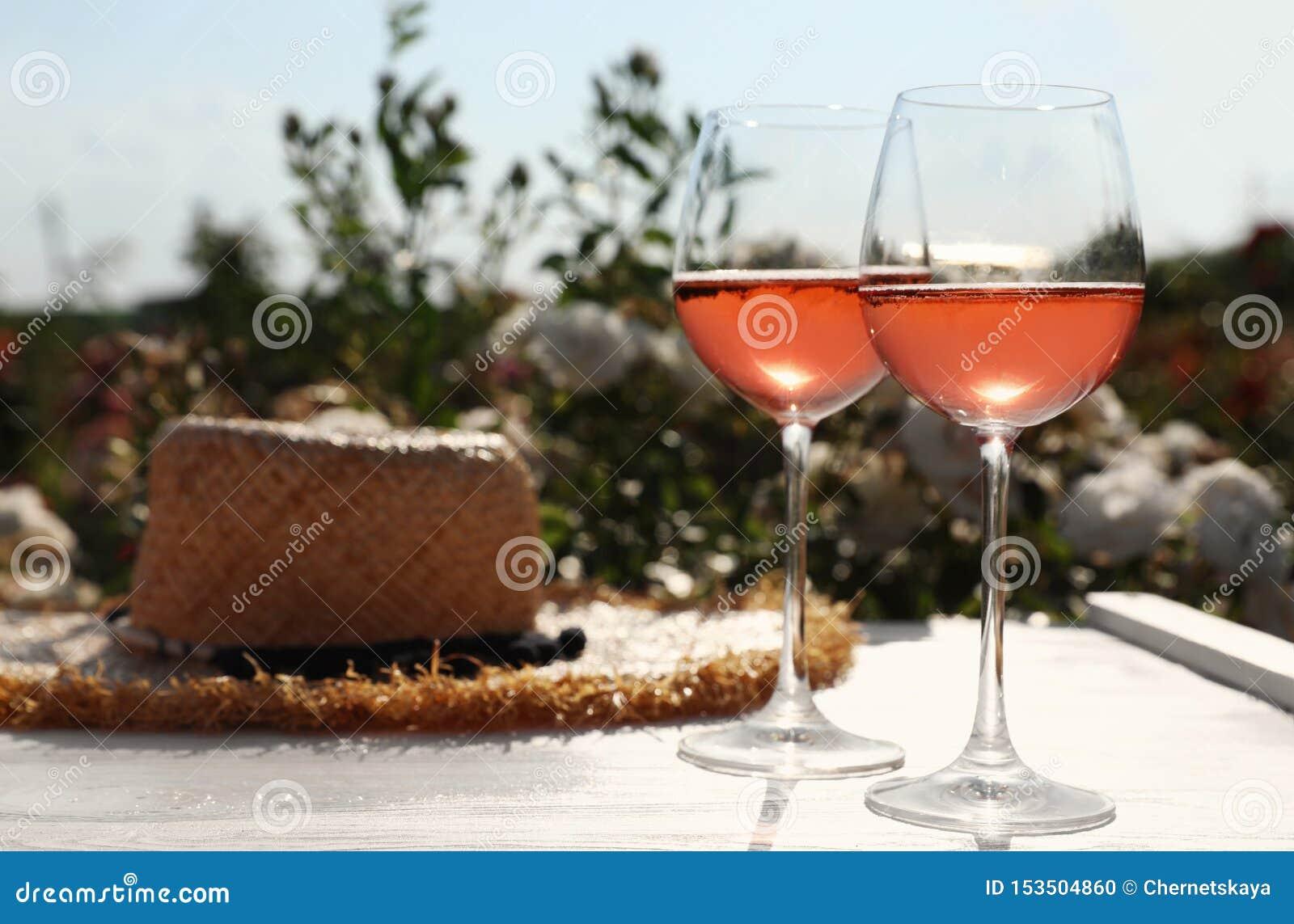 Стекла розового вина и соломенной шляпы на белом деревянном столе outdoors