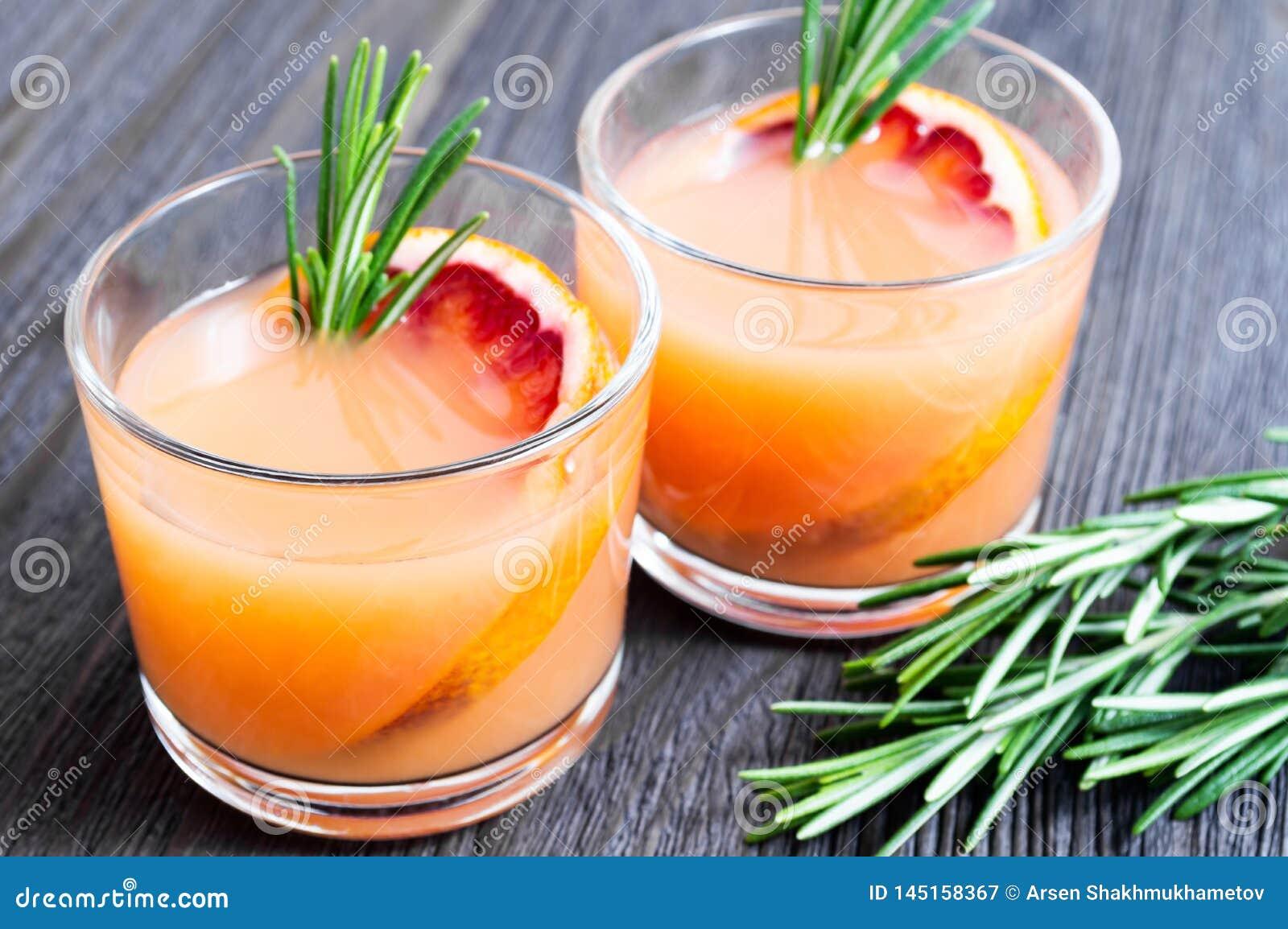 2 стекла свежего напитка лета с апельсином и розмариновым маслом крови на темной деревянной предпосылке r