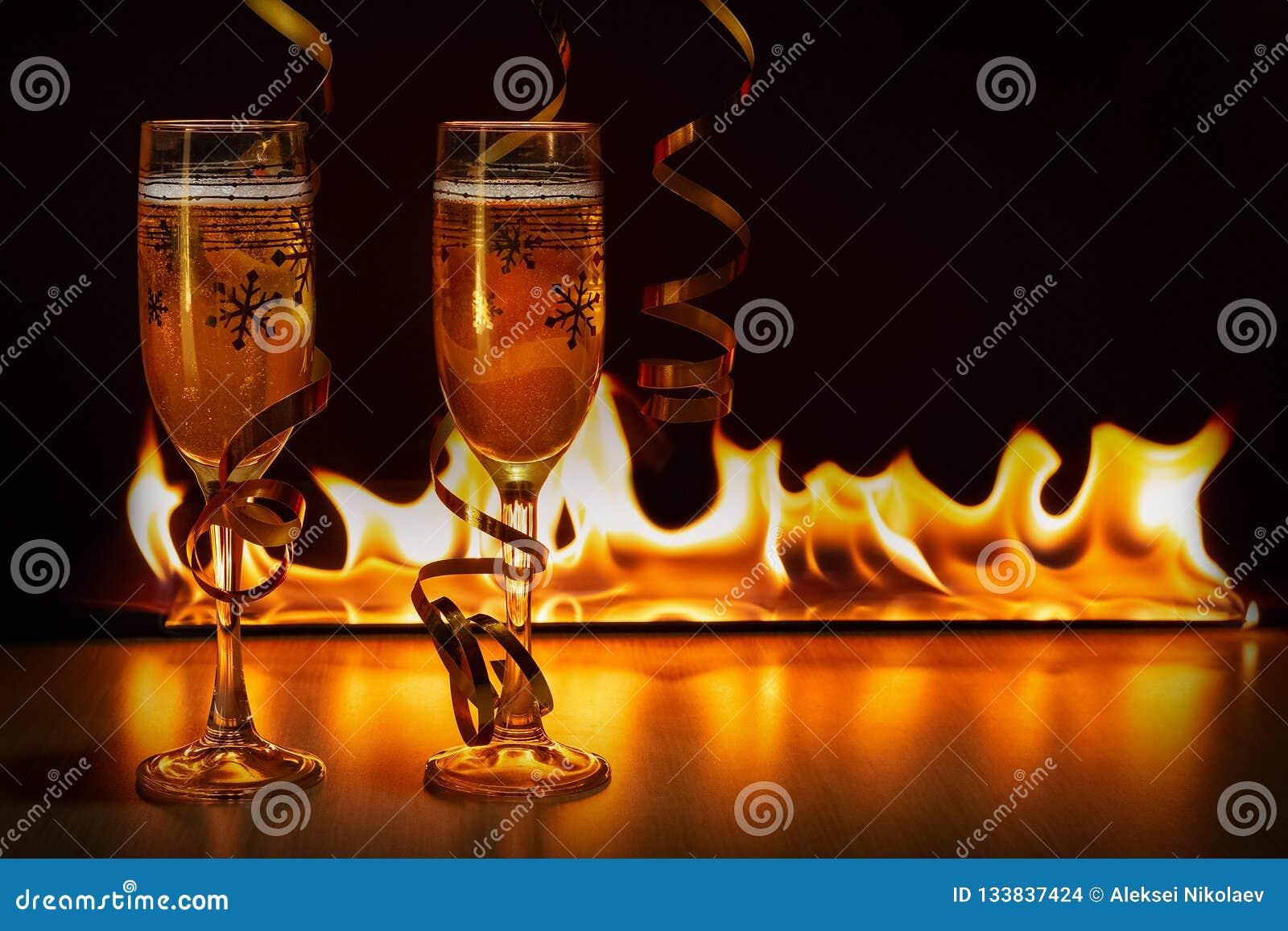 2 стекла сверкная шампанского с золотыми лентами против предпосылки bokeh ярких пламен создавая уютное