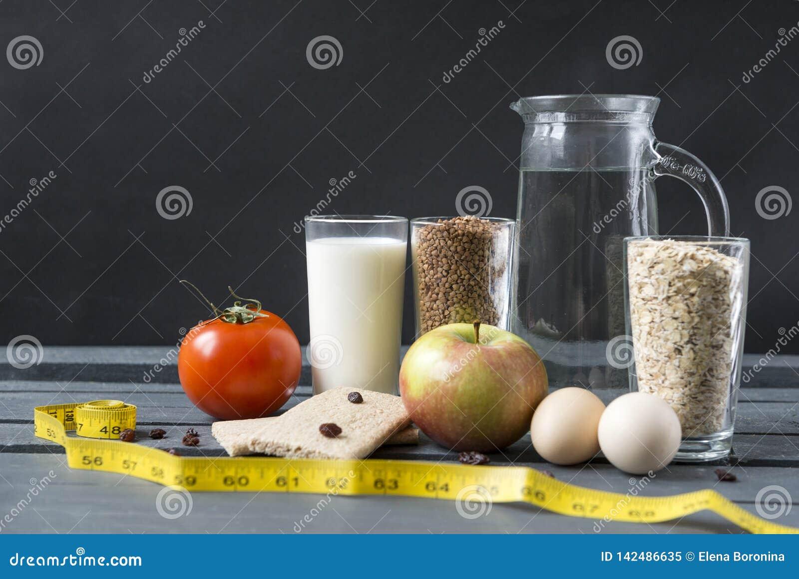 Стекла с молоком, гречихой, хлопьями овса, графинчиком воды, красным томатом, Яблоком, 2 яйцами, хлебом, изюминками, измеряя лент