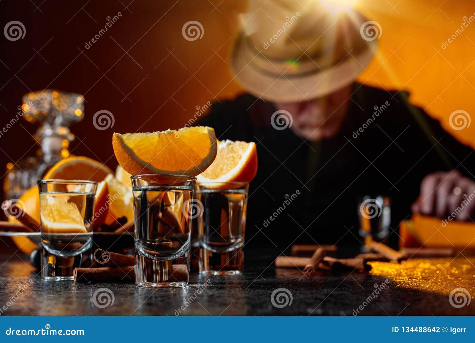 Стекла текила с ручками апельсина и циннамона на таблице в баре