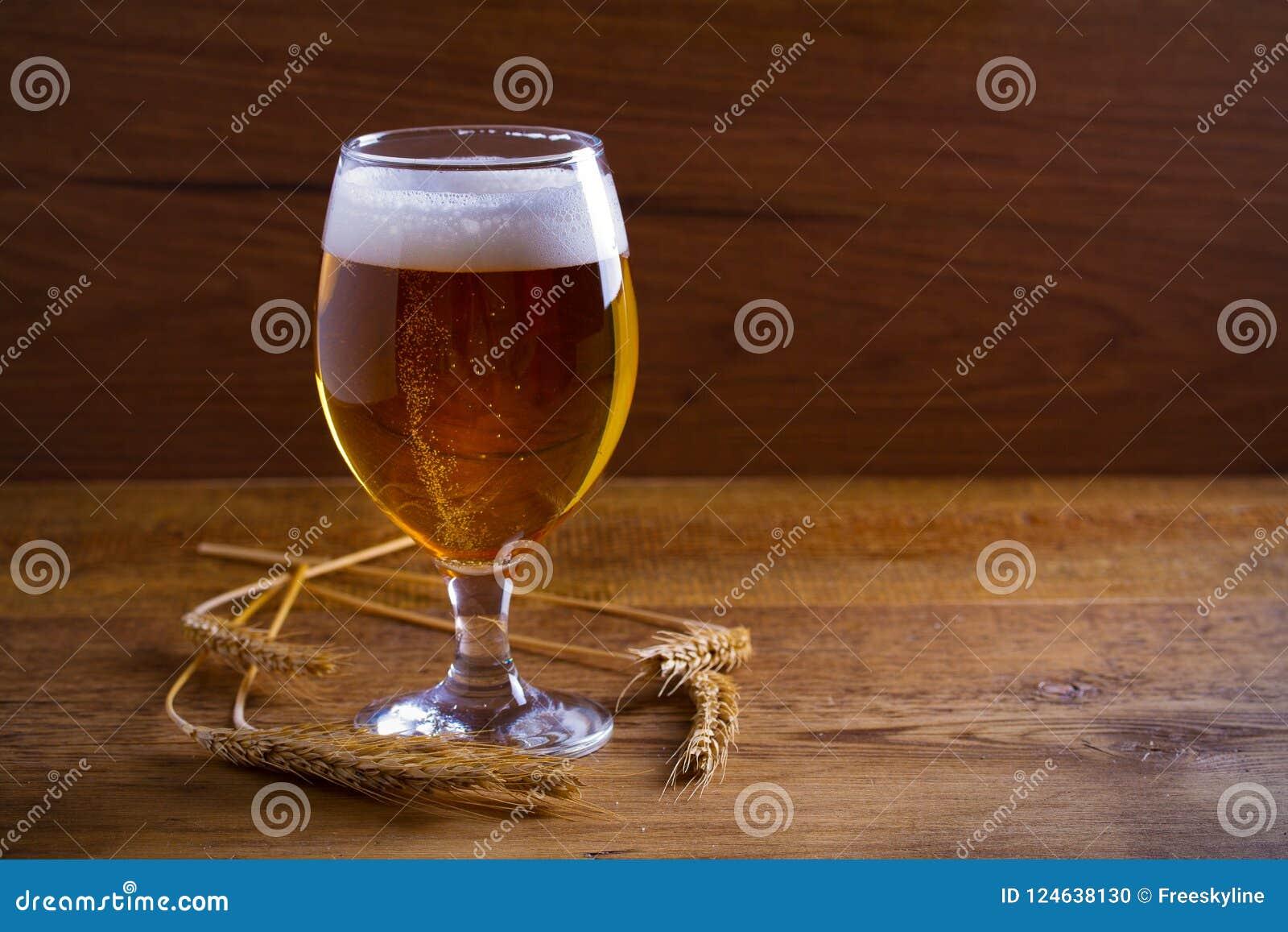 Стекло и бутылка пива, ушей ячменя на деревянной предпосылке aleppo