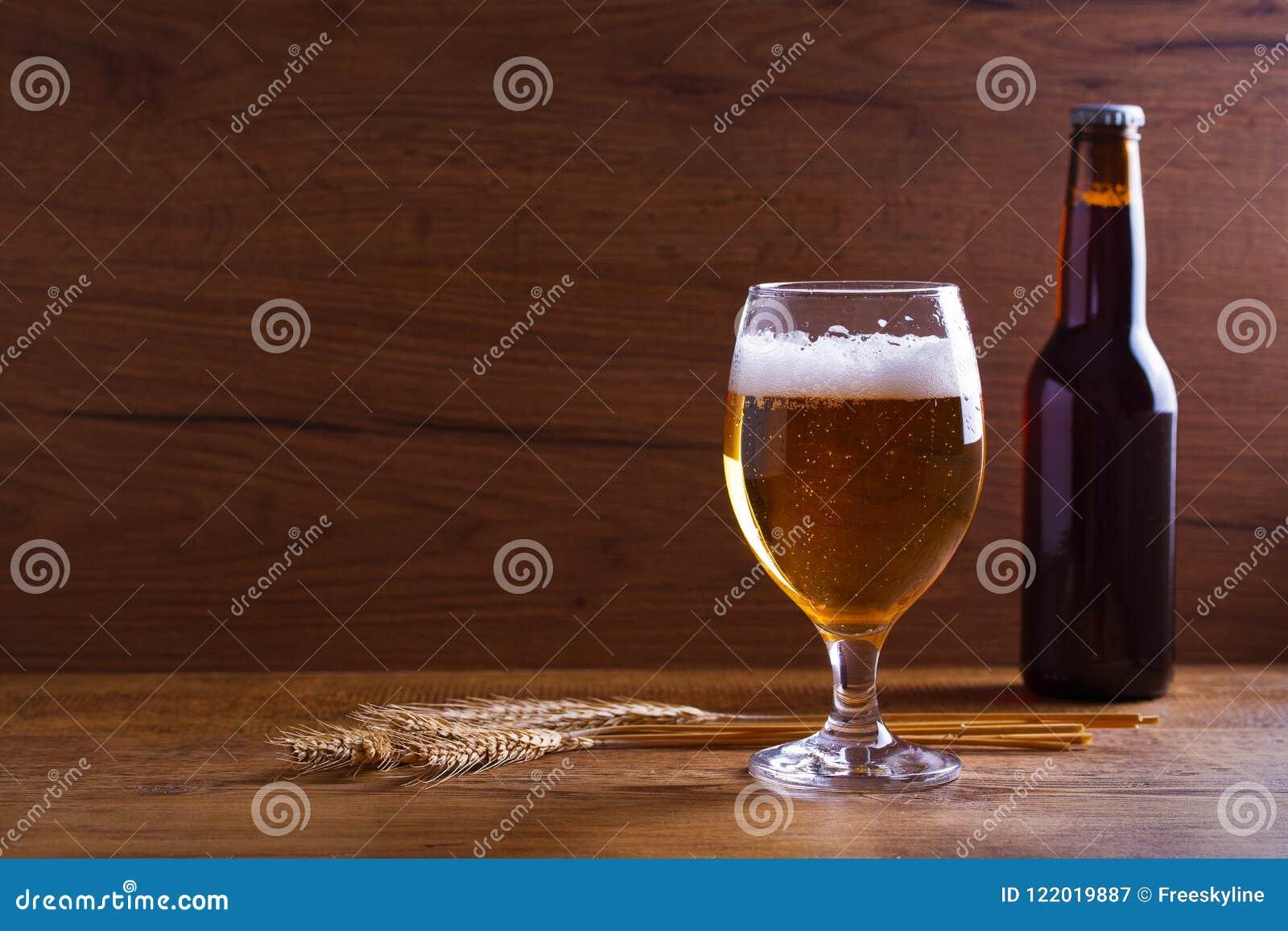 Стекло и бутылка пива, ушей ячменя на деревянном столе aleppo