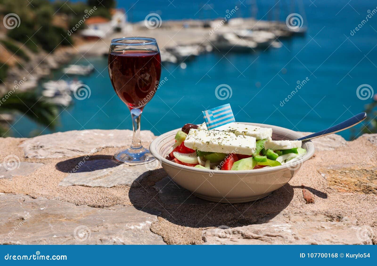 Стекло красного вина и шара греческого салата с греческим флагом дальше видом на море, концепцией праздников лета греческой