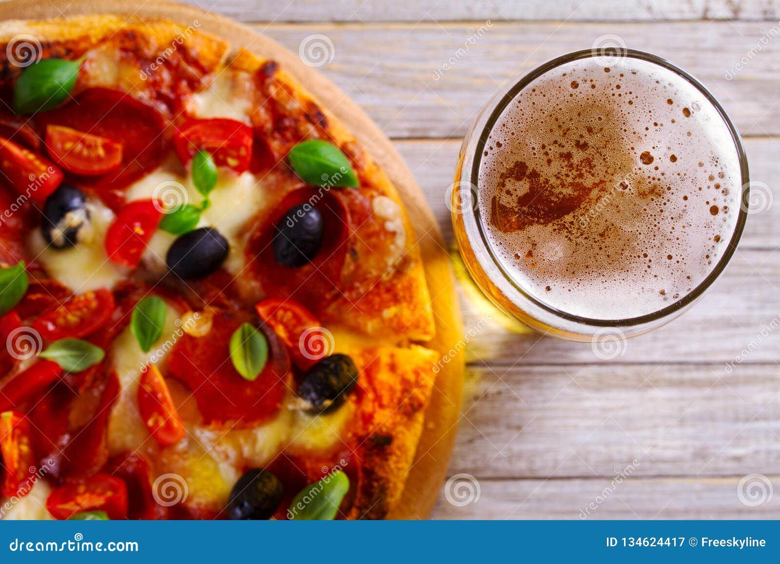 Стекло пива и пиццы на деревянном столе Концепция пива и еды aleppo