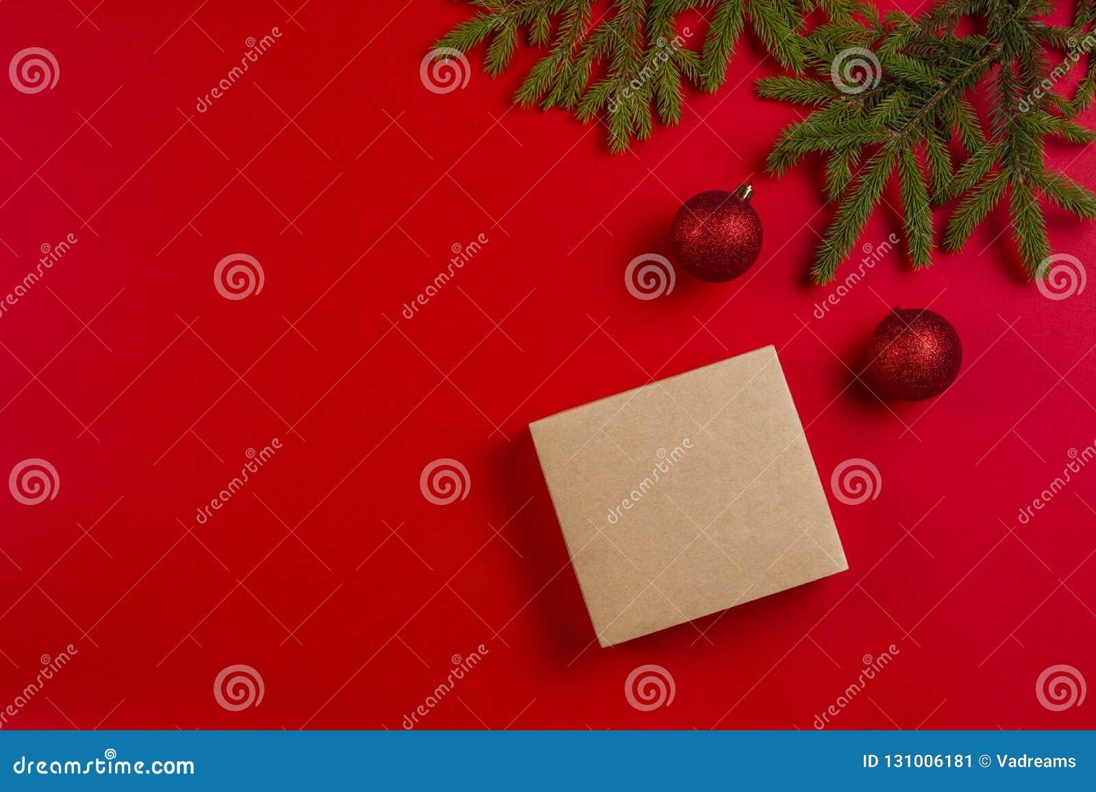 стекло состава рождества bauble голубое Ветви ели, украшения рождества и присутствующая подарочная коробка на красной предпосылке