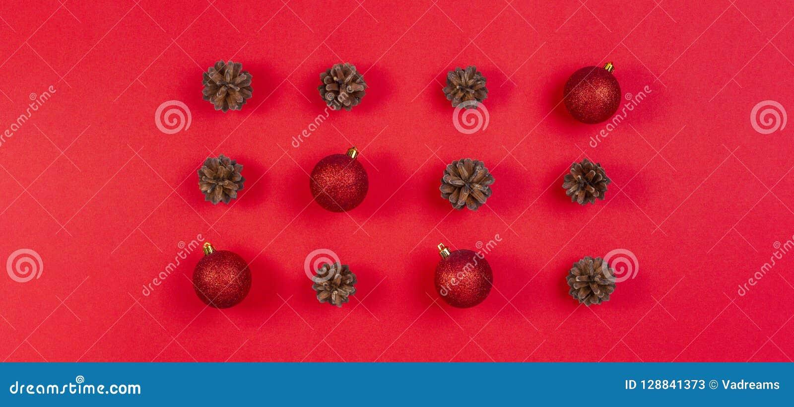стекло состава рождества bauble голубое Картина сделанная конусов сосны и красного украшения рождества на красной предпосылке Взг