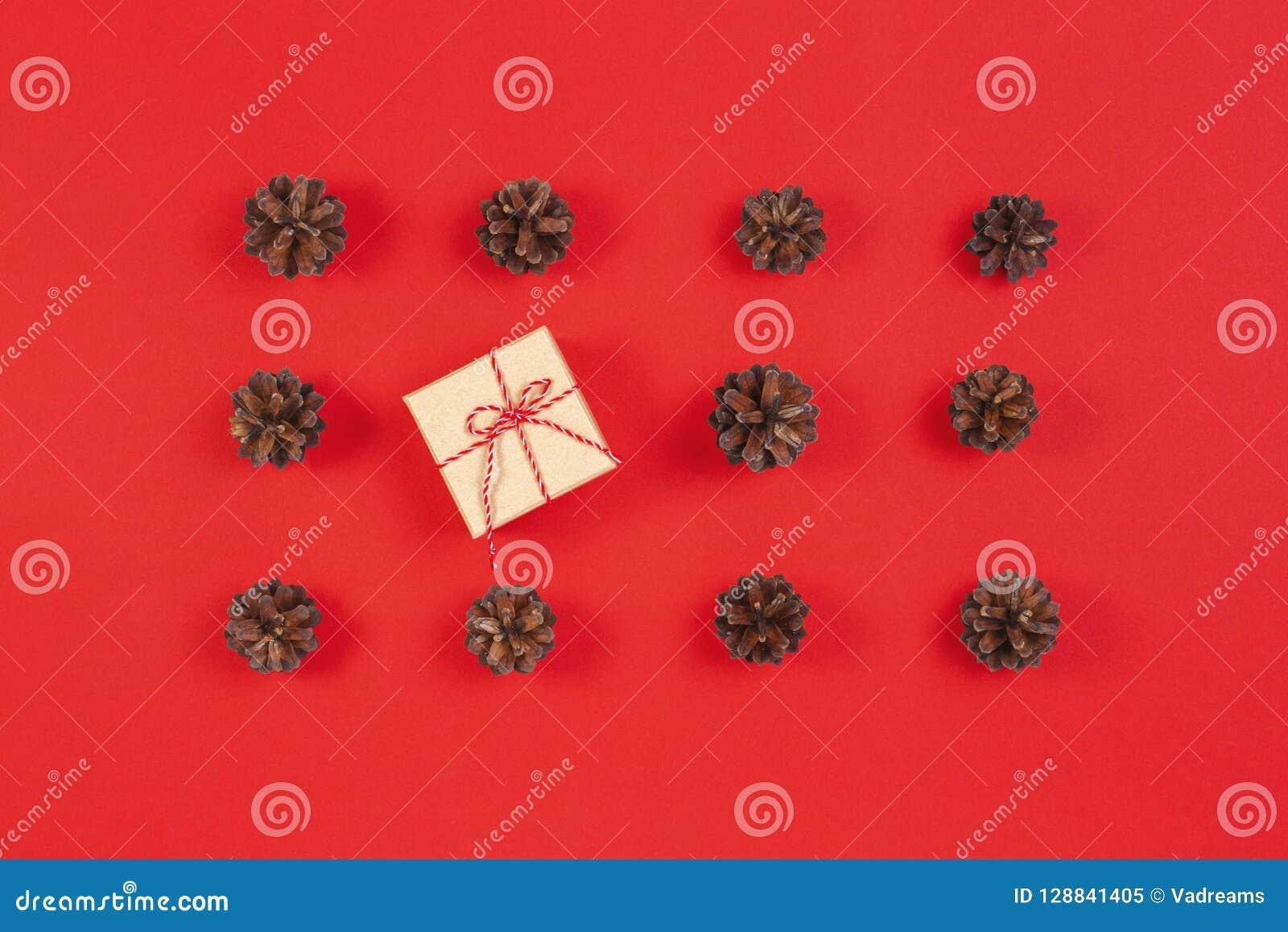 стекло состава рождества bauble голубое Картина сделанная конусов сосны, подарочная коробка украшения рождества на красной предпо