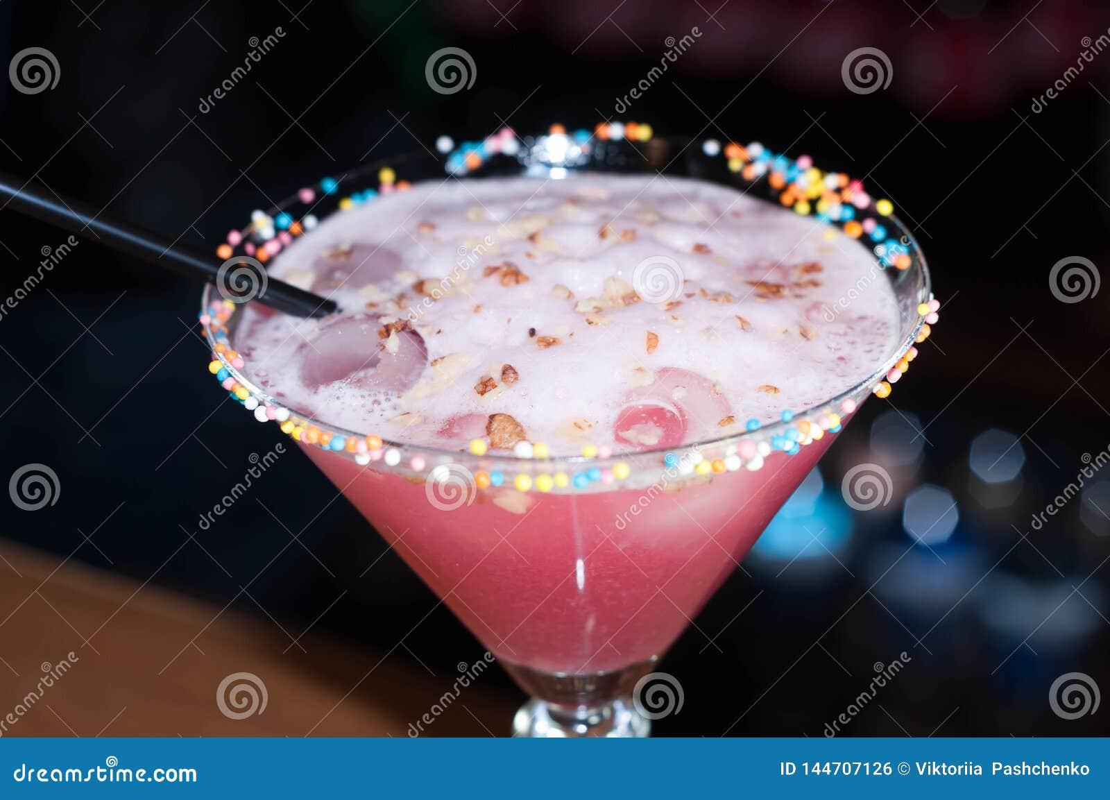 Стекло с красными напитком и соломой алкоголя
