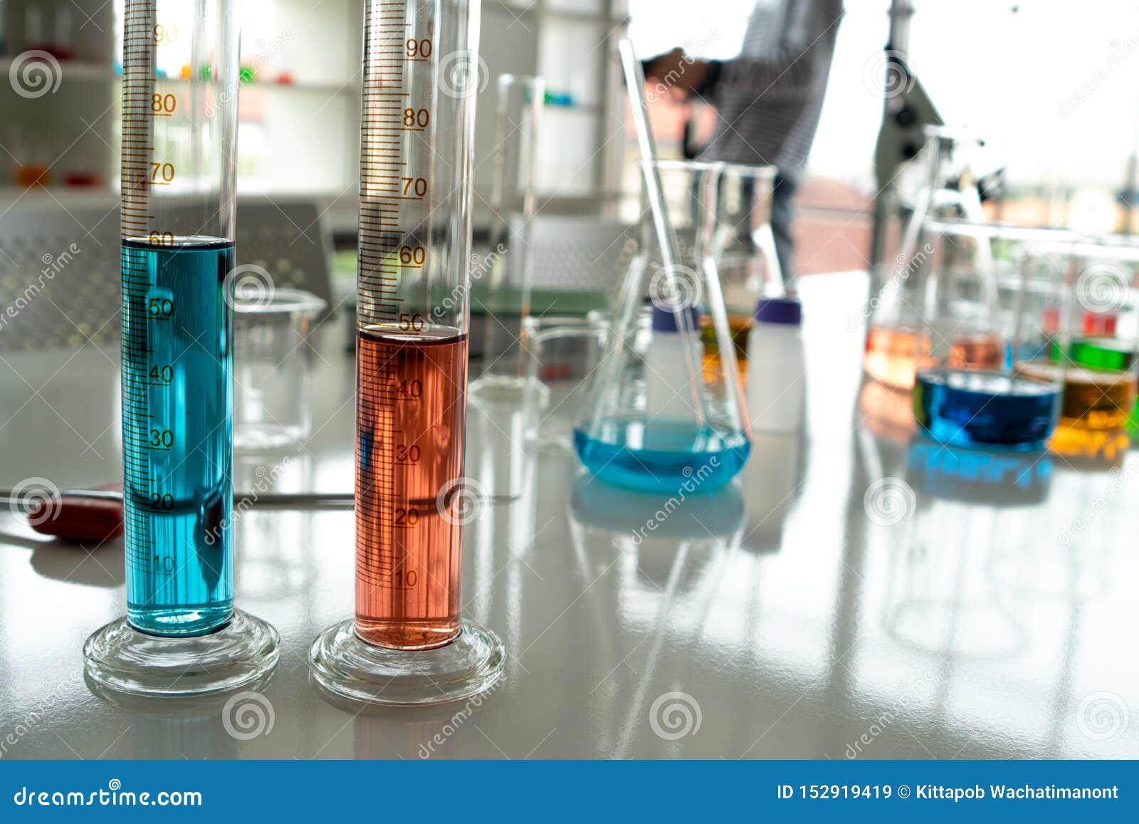 Стеклянные лампы, много пробирок в лаборатории которые содержат различные цвета жидкости