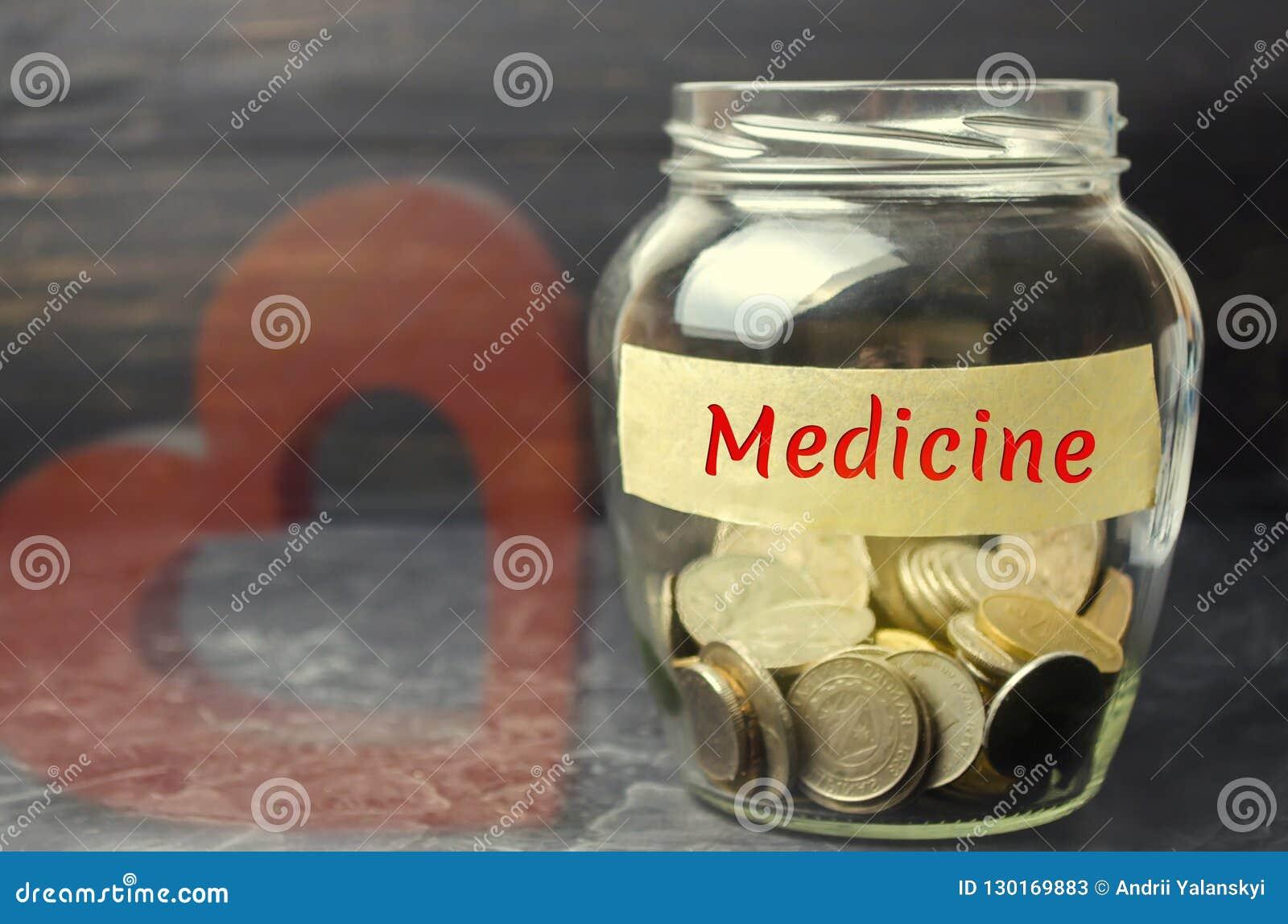 """Стеклянный опарник с монетками и надписью """"медицина """" Концепция страхования семейной медицины, здравоохранения Медицинские расход"""