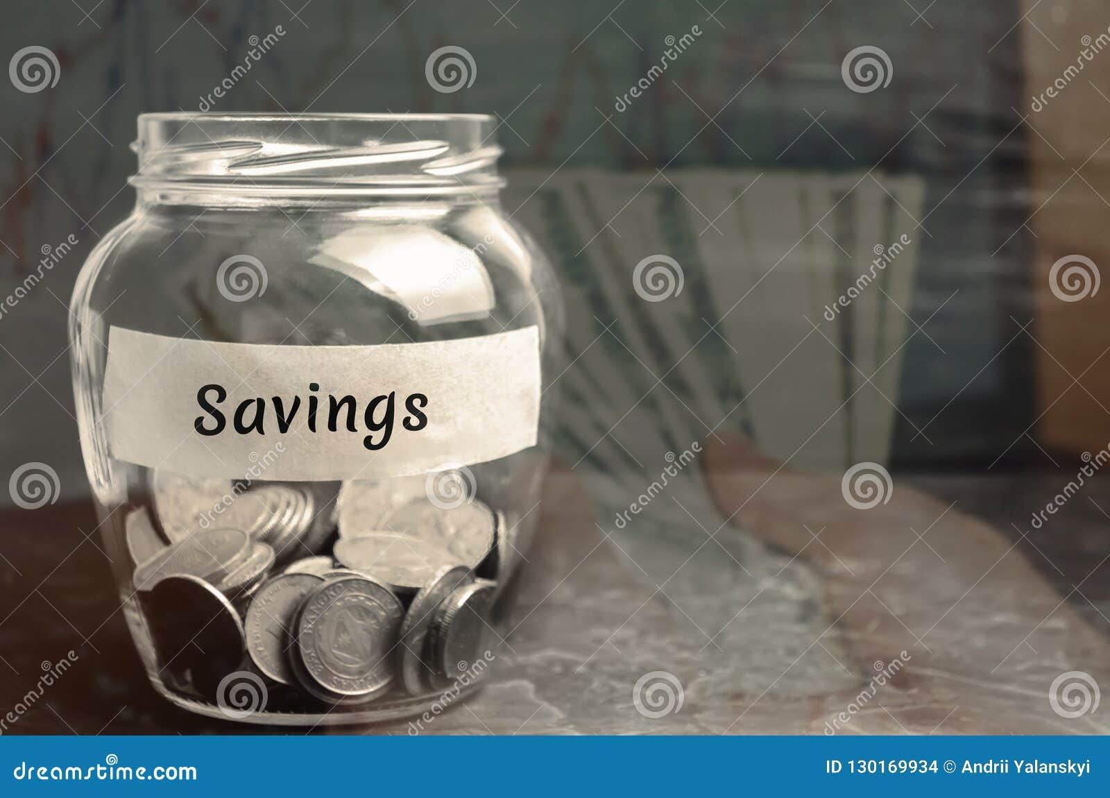 """Стеклянный опарник с монетками и надписью """"сбережения """" Концепция аккумулировать деньги в семейном бюджете Страхование семьи dist"""
