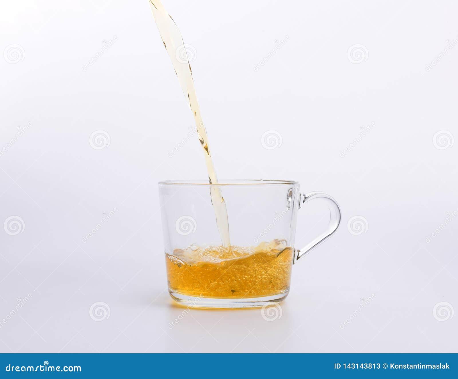Стеклянный чайник лить зеленый чай в чашку изолированную на белой предпосылке