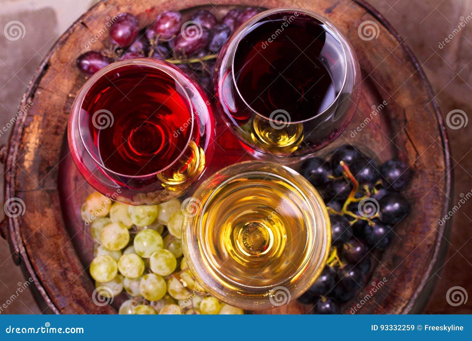 Стекла вина красного цвета, розовых и белых с виноградиной в винном погребе Еда и концепция пить
