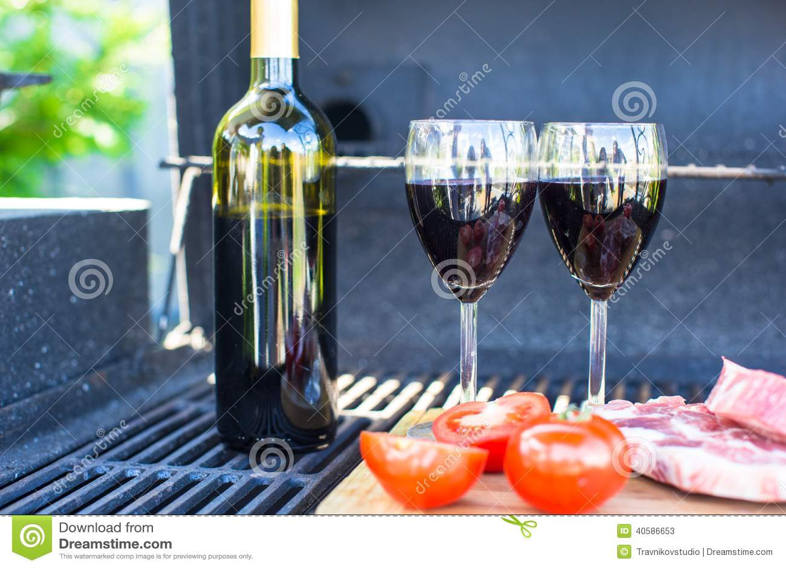 2 стекла красного вина, стейка и томатов на барбекю outdoors