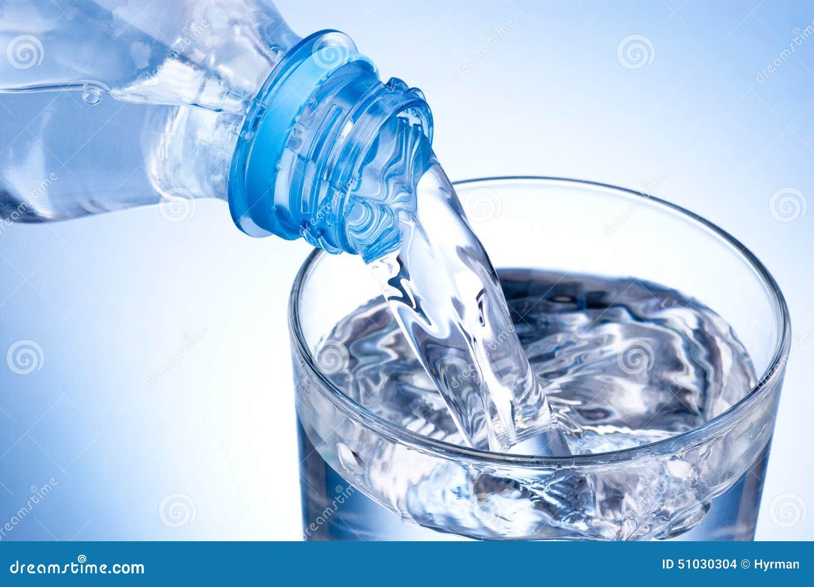 Стекло конца-вверх лить воды от пластичной бутылки на голубой предпосылке