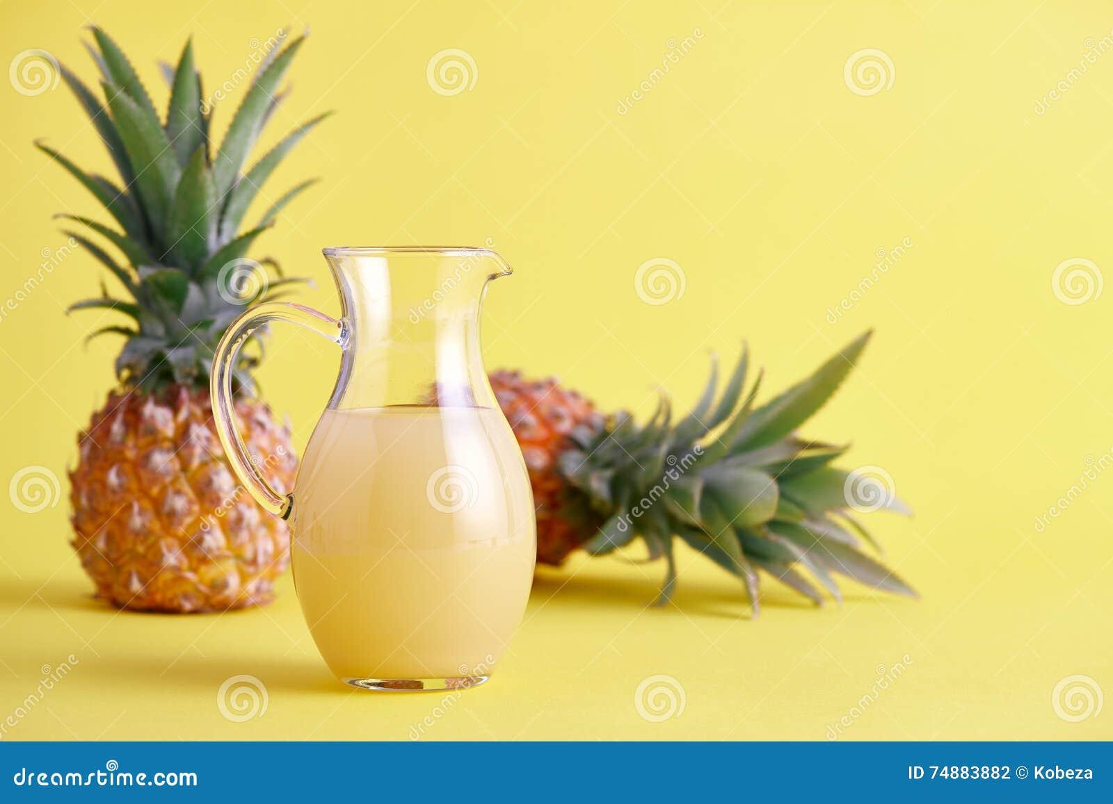 Стеклянный кувшин свежего сока ананаса на желтом цвете